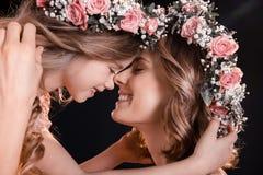 Madre e hija felices en las guirnaldas florales que abrazan en negro Fotos de archivo libres de regalías