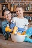 Madre e hija felices en los guantes de goma con las fuentes de limpieza Imagenes de archivo