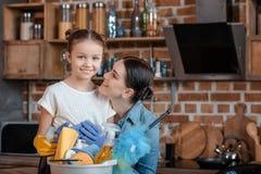 Madre e hija felices en los guantes de goma con las fuentes de limpieza Fotografía de archivo libre de regalías