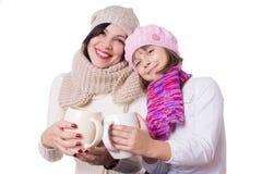 Madre e hija felices en sombreros hechos punto con las bebidas calientes Foto de archivo