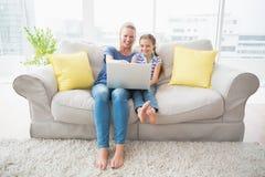 Madre e hija felices que usa el ordenador portátil en el sofá Fotografía de archivo