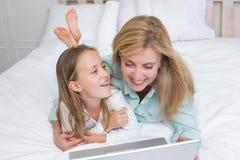 Madre e hija felices que usa el ordenador portátil Imagen de archivo