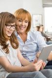 Madre e hija felices que usa la tableta con la familia que se sienta en fondo en casa Fotos de archivo libres de regalías