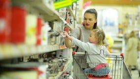 Madre e hija hermosas dentro del hipermercado que elige un poco de cacerola roja y que la pone en carro de la compra almacen de metraje de vídeo