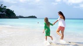 Madre e hija hermosas en la playa del Caribe Familia que camina en la costa tropical Cámara lenta almacen de video