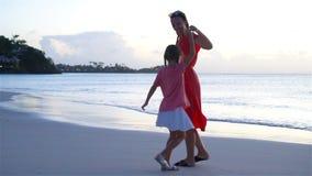 Madre e hija hermosas en la playa del Caribe que se divierte en puesta del sol Familia el vacaciones de la playa Cámara lenta almacen de metraje de vídeo