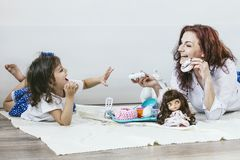 Madre e hija hermosas jovenes de la mujer con los platos del juguete, dulces Foto de archivo