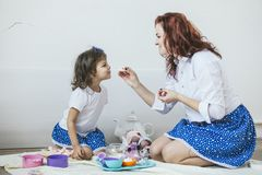 Madre e hija hermosas jovenes de la mujer con los platos del juguete, dulces Fotos de archivo