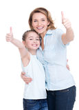 Madre e hija joven con los pulgares para arriba imagenes de archivo