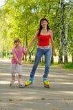 Madre e hija jovenes con los rodillos Imagenes de archivo