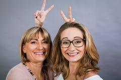 Madre e hija jovenes de mediana edad sonrientes Foto de archivo