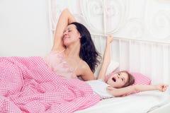 Madre e hija jovenes en cama Foto de archivo libre de regalías