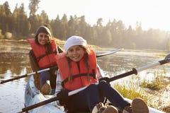 Madre e hija kayaking en el lago rural, cierre para arriba Imagen de archivo