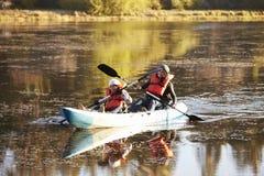 Madre e hija kayaking junto en un lago, cierre para arriba Foto de archivo libre de regalías