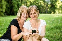 Madre e hija mayores con smartphone Fotos de archivo libres de regalías