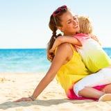 Madre e hija modernas felices en el abarcamiento de la playa Fotografía de archivo