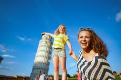 Madre e hija modernas sonrientes que presentan para la imagen turística imagenes de archivo