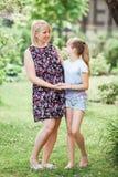 Madre e hija Mujer embarazada hermosa en vestido de maternidad floral corto y el niño que miran el uno al otro y que sonríen fotos de archivo