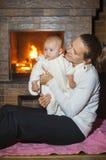 Madre e hija por la chimenea en invierno Fotos de archivo