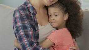 Madre e hija que abrazan en casa, cuidado y ayuda, dulzura de la familia metrajes