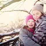 Madre e hija que abrazan en día de invierno Imagenes de archivo
