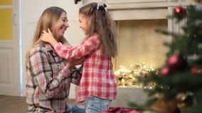 Madre e hija que abrazan en la Navidad en casa metrajes