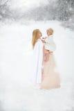 Madre e hija que abrazan feliz en tormenta de la nieve Imagen de archivo