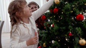 Madre e hija que adornan el árbol de navidad en casa almacen de metraje de vídeo