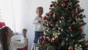 Madre e hija que adornan el árbol de navidad en víspera el día de fiesta del Año Nuevo metrajes