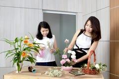 Madre e hija que arreglan las flores en la tabla de madera Foto de archivo libre de regalías