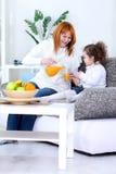Madre e hija que beben el zumo de naranja fotos de archivo