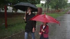 Madre e hija que caminan en la calle en fuertes lluvias metrajes