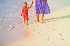 Madre e hija que caminan en la playa que deja huella en arena Foto de archivo