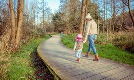 Madre e hija que caminan juntas llevando a cabo las manos Fotografía de archivo libre de regalías