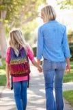 Madre e hija que caminan a la escuela en la calle suburbana Imagenes de archivo
