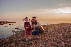 Madre e hija que caminan a lo largo de la playa en la puesta del sol El concepto de una familia amistosa feliz foto de archivo