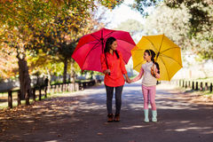 Madre e hija que celebran los paraguas en el parque Fotos de archivo libres de regalías
