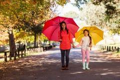 Madre e hija que celebran los paraguas en la calle en el parque Imagen de archivo libre de regalías