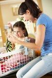 Madre e hija que clasifican el lavadero Fotos de archivo libres de regalías