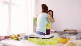 Madre e hija que cocinan y que abrazan en casa almacen de video