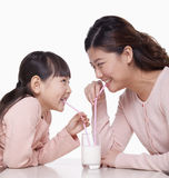 Madre e hija que comparten un vidrio de leche, tiro del estudio Foto de archivo libre de regalías