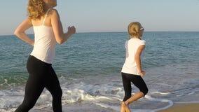 Madre e hija que corren en la playa almacen de video