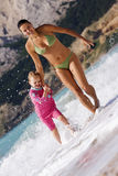Madre e hija que corren en la playa foto de archivo