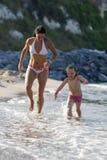 Madre e hija que corren en la playa imágenes de archivo libres de regalías