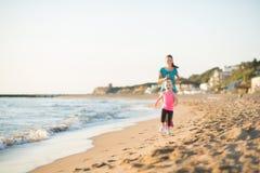 Madre e hija que corren a lo largo del agua en la playa en la puesta del sol Fotos de archivo