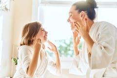 Madre e hija que cuidan para la piel imagenes de archivo