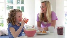 Madre e hija que desayunan en cocina junto almacen de metraje de vídeo
