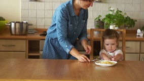 Madre e hija que desayunan sano en cocina La muchacha no tiene hambre Ella rechaza comer, empuja la placa almacen de metraje de vídeo