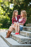 Madre e hija que descansan en parque del verano Imagen de archivo
