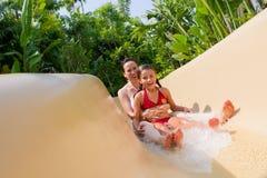 Madre e hija que deslizan abajo la diapositiva de agua. Fotos de archivo
